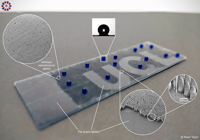 A smart glass prototype developed by the UCL team. The dark areas are decorated with the nanostructures, which significantly suppress reflections. They also repel water forcing it to form nearly spherical droplets and preventing it from wetting the surface of the glass. The UCL logo is made of untreated glass and appears significantly more reflective compared with its surrounding region (UCL)